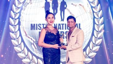 Sandeep Kumar receiving the Best Pageant Director award from the owner of Mister National Universe pageant, Tanya V in Thailand.